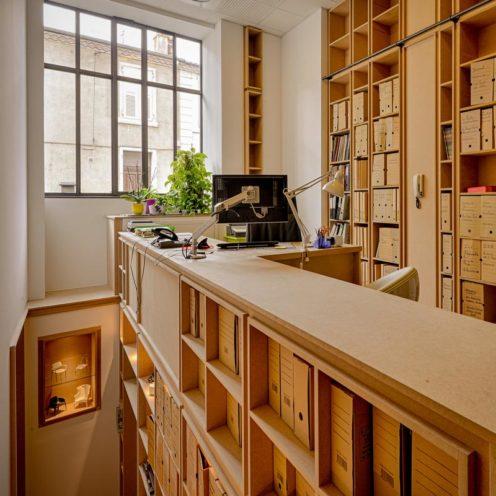 Un bureau sur-mesure en bois intégré à la bibliothèque de l'escalier par Vallon Faure